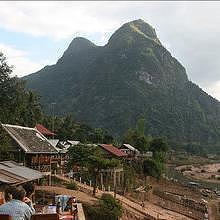 "Sitting in a restaurant in Muang Ngoi, in front of the holly mountain named ""young girl"" for its languorous shape"