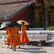 Monks passing by the Vat Mai temple in Luang Prabang